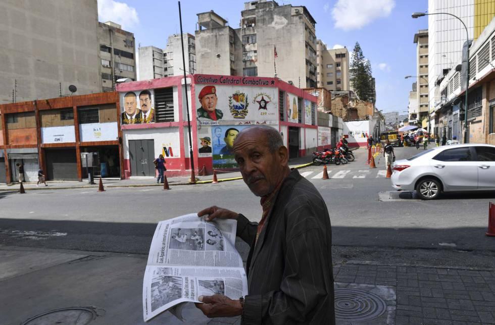 Un hombre lee un periódico, ayer en una calle de Caracas.
