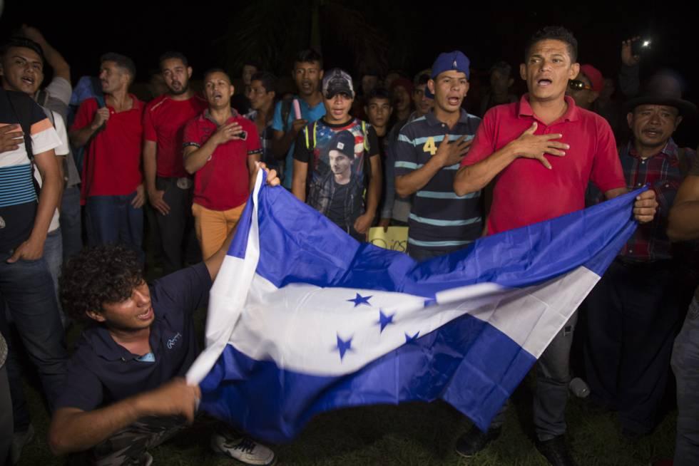 Miembros de la caravana ondean una bandera hondureña.