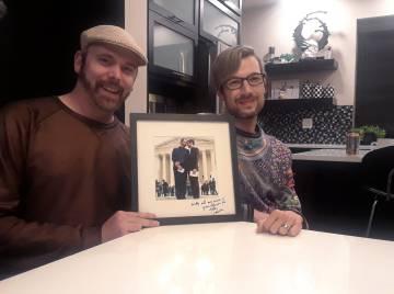 Charlie Craig y Dave Mullins enseñan una fotografía de su boda.