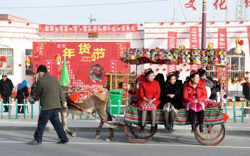 Unas ciudadanas chinas son transportadas en un carro tirado por un burro, a finales del pasado enero en Lopnur (Xinjiang).