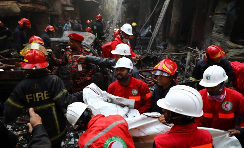 Un grupo de voluntarios rescata un cuerpo del incendio en Bangladesh.