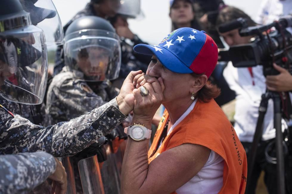 Una mujer suplica a un miembro de la Policía Nacional Bolivariana que deje pasar la ayuda humanitaria.