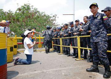 Una seguidora de Juan Guaidó se arrodilla frente a agentes de la Guardia Nacional Bolivariana.