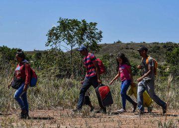 Venezolanos caminan en Pacaraima, Brasil, tras cruzar la frontera.