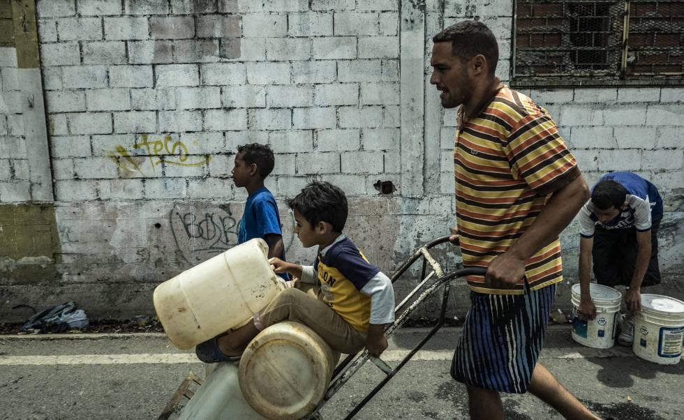 Un hombre y sus hijos portan garrafas de agua en Caracas.