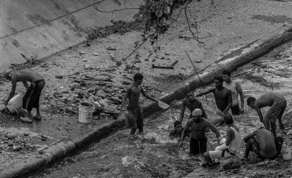 Jóvenes buscan objetos de valor en las aguas del Río Guaire.