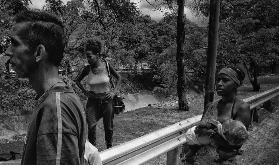 Una familia recolecta agua de un cauce en Caracas.