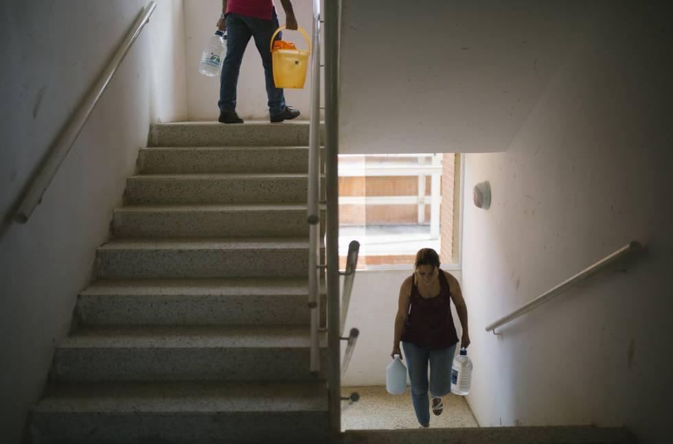 Yelitza Izalla y Carlos Guerra suben recipientes llenos de agua a su apartamento.
