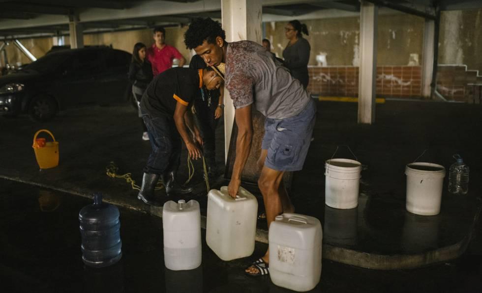 Vecinos de la urbanización El Encantado, en Caracas, llenan recipientes de agua.