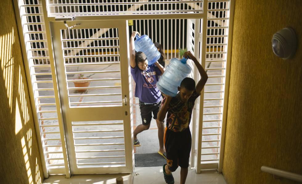 Dos jóvenes suben agua a sus casas.