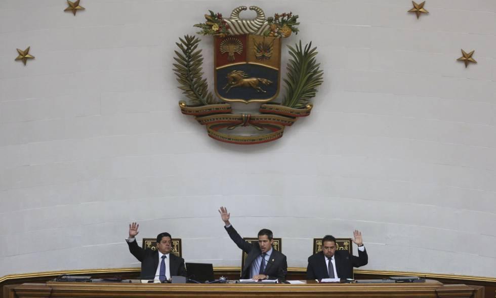 Juan Guaidó (centro) alzan sus manos en una sesión de la Asamblea Nacional venezolana.