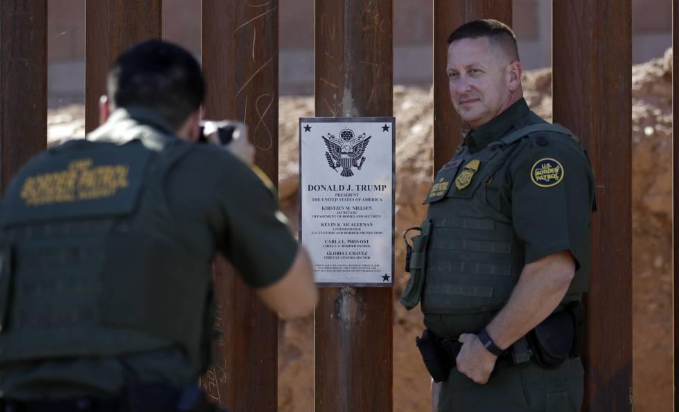 Dos agentes de la policía fronteriza se hacen fotos el pasado octubre en el trozo de valla que Trump visitó este viernes.