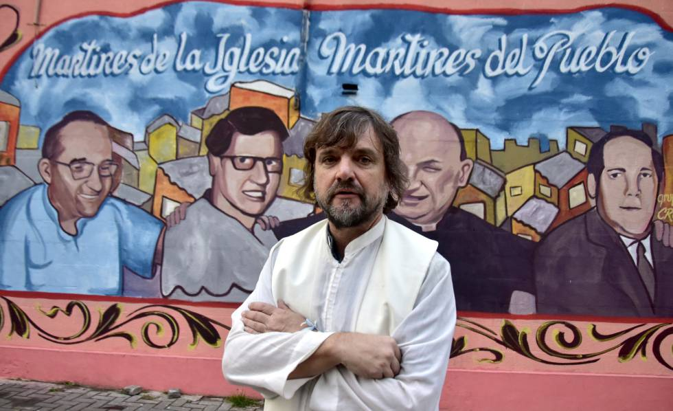 El padre José María Di Paola posa frente al mural que recuerda al obispo Angelelli