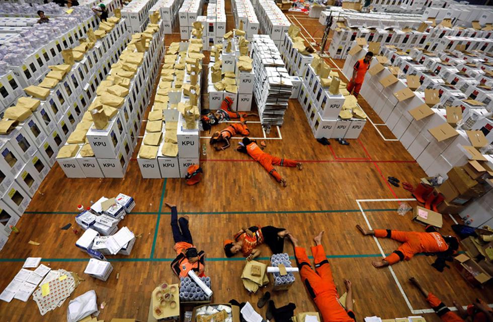 Varios trabajadores descansan en el suelo rodeados de material electoral, en Yakarta.