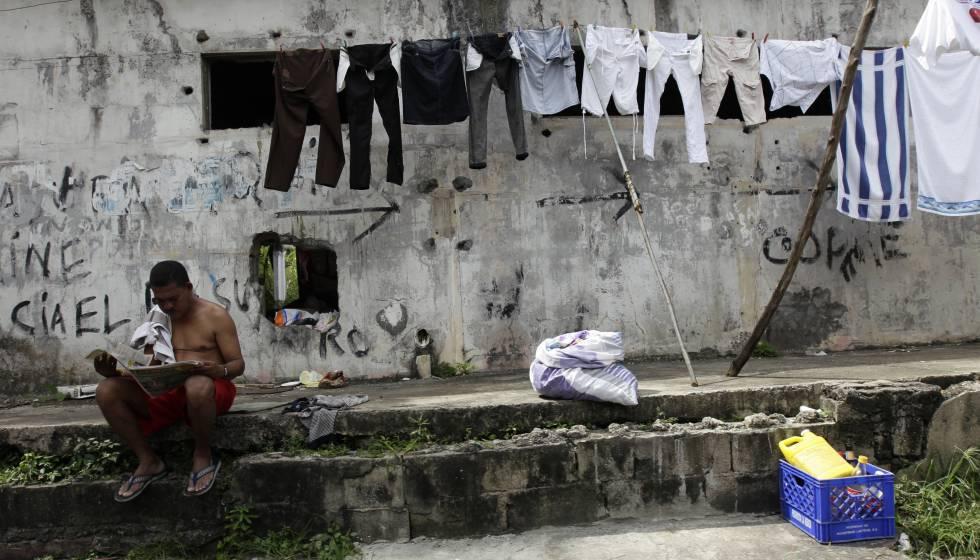 Un panameño lee el periódico frente a la ropa tendida.