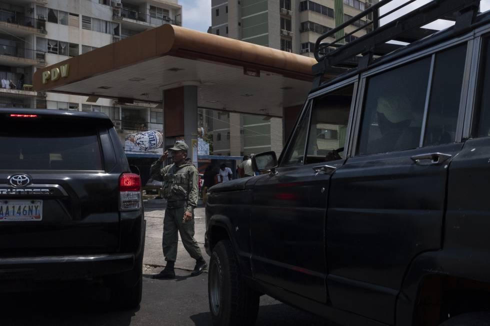 Un soldado saluda al conductor de una camioneta frente a una bomba de gasolina en Maracaibo.
