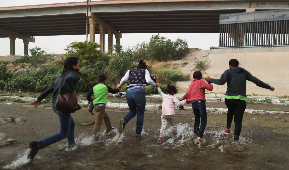 Un grupo de inmigrantes cruza el río entre Ciudad Juárez y El Paso, este lunes.