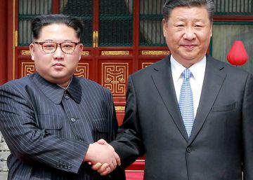 Kim Jong-un y Xi Jinping se saludan durante la visita del primero a Pekín el 27 de marzo de 2018.