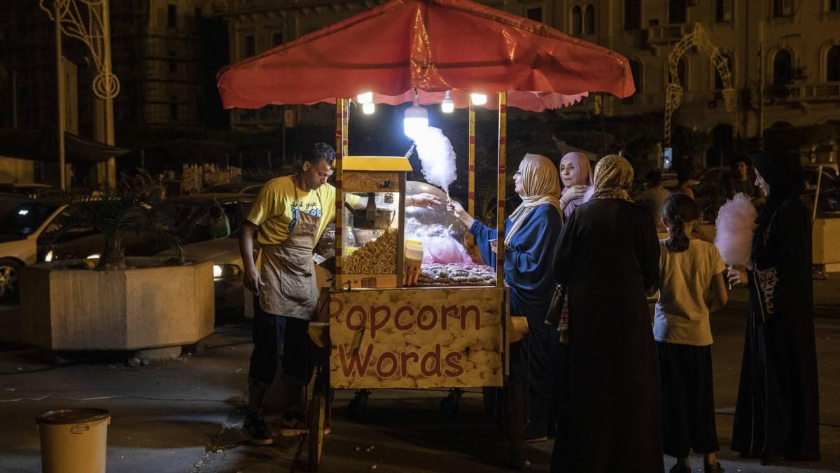 Varias mujeres ante un puesto de palomitas en Trípoli.