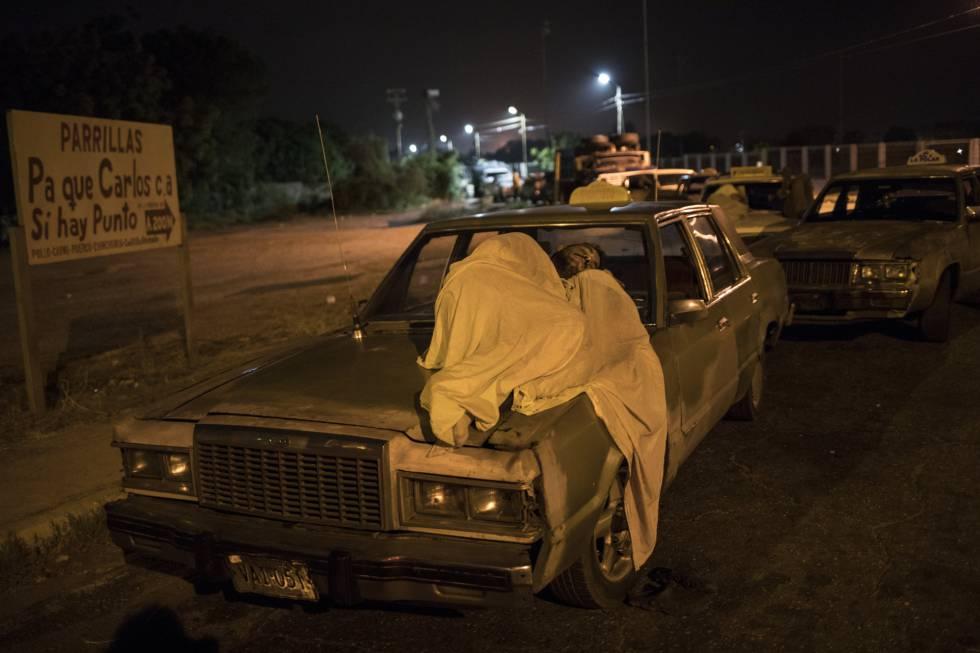 Un hombre duerme sobre su auto mientras espera por gasolina en Maracaibo.