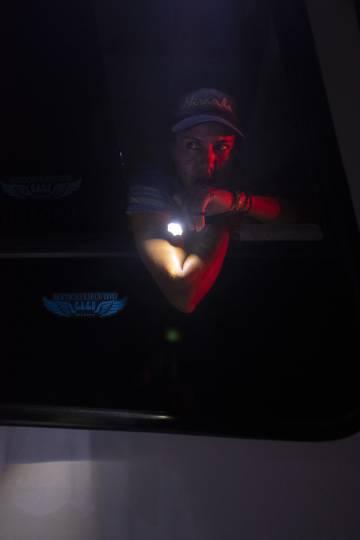 La copiloto de un autobús ilumina a los pasajeros que abordan, en Caracas.