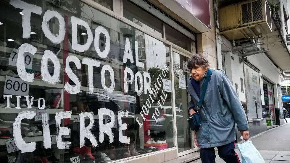 Mulher passa diante de loja em liquidação no dia 22 de agosto, em Buenos Aires. Em vídeo, imagens dos protestos na Argentina.