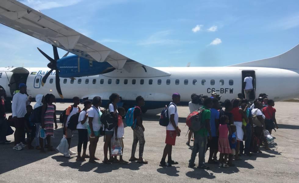 Vecinos evacuados en un avión, en el aeropuerto de Treasure Cay.