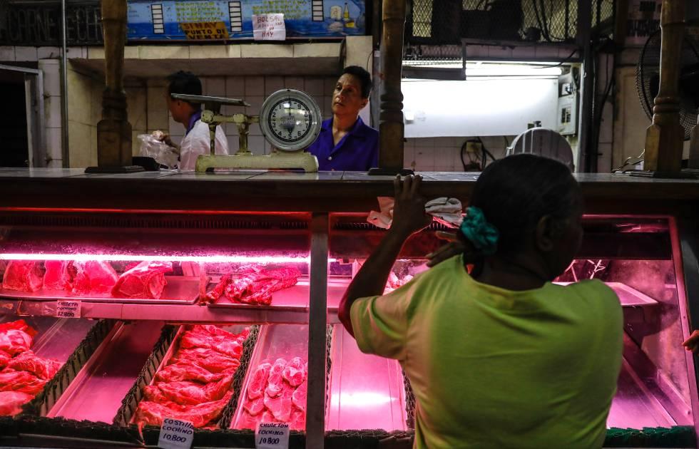 Una mujer compra carne en un establecimiento de Carcas.