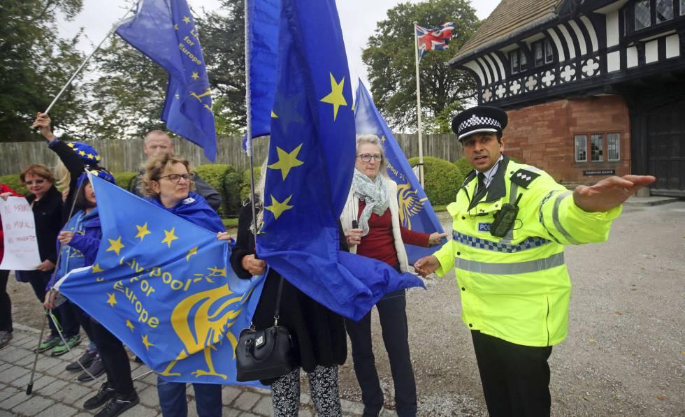 Un policía desvía a los manifestantes concentrados este jueves ante la residencia de Wirral (Reino Unido) donde se han reunido Johnson y Varadkar.