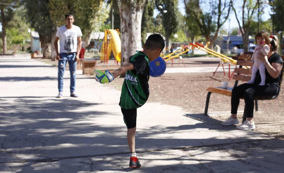 Un niño juega con su padre a la pelota en la plaza de Añelo.
