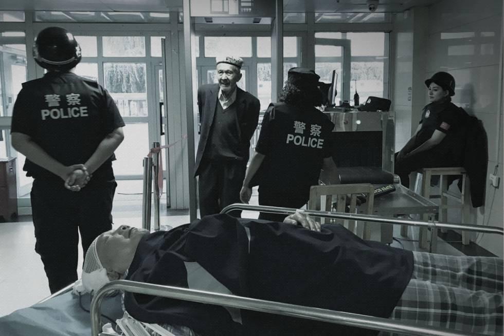 Un hombre uigur pasa por un control de seguridad para entrar en un hospital, en Xinjiang.