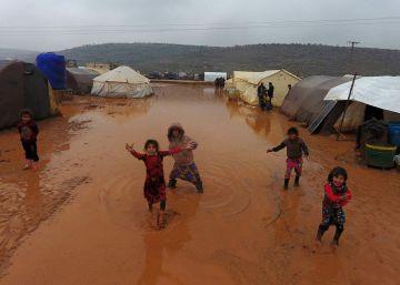 Niños sirios junto a las tiendas de un campamento de refugiados inundado, el domingo en Idlib.