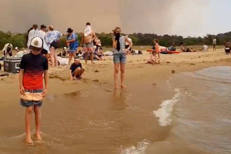 Un grupo de gente se refugia este martes de los incendios en Batemas Bay (Australia).