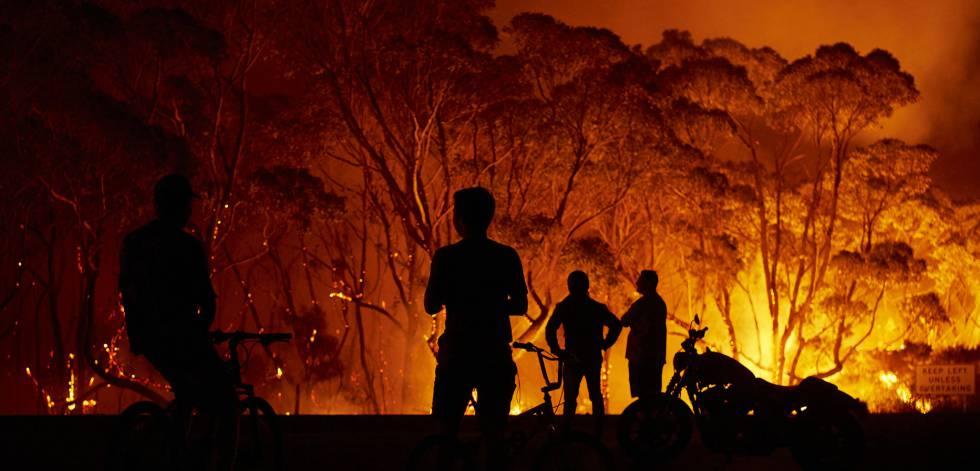 Unos vecinos observan las llamas en torno a su localidad, este sábado en Tabourie Lake (Nueva Gales del Sur).