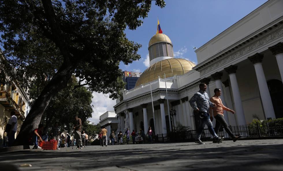 Dos personas caminan afuera de la Asamblea Nacional de Venezuela.