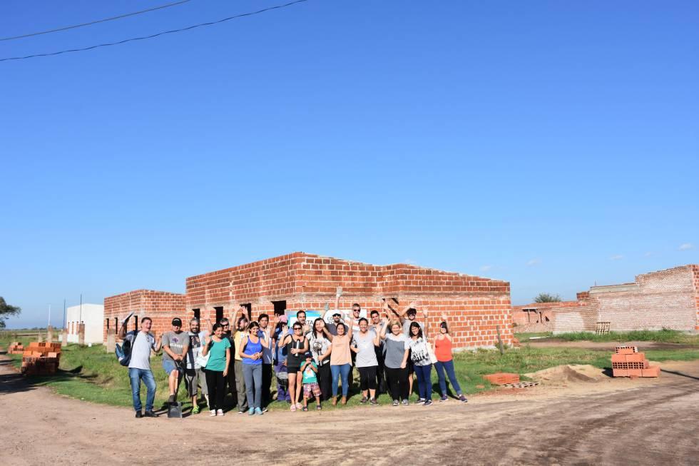 Familias seleccionadas para el proyecto 'Bienvenidos a mi pueblo' frente a las casas en construcción.