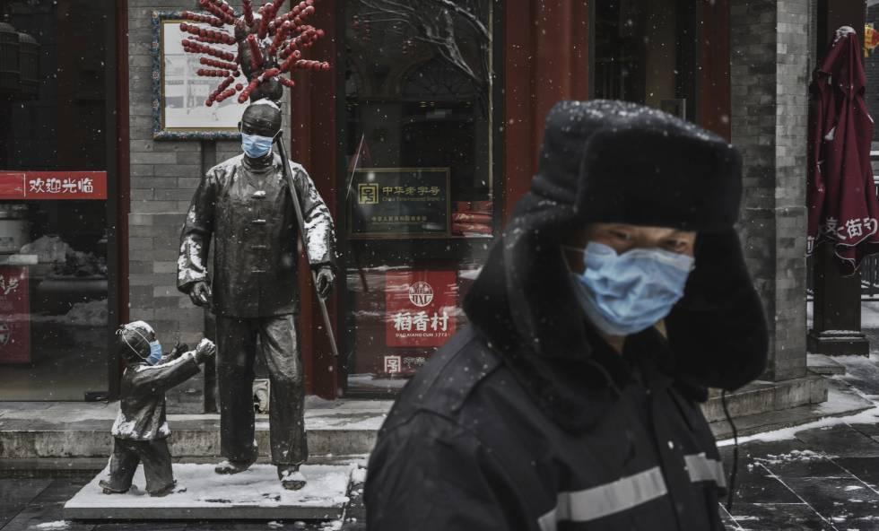 Un hombre con mascarilla en una calle de Pekín con los establecimientos cerrados, el miércoles.