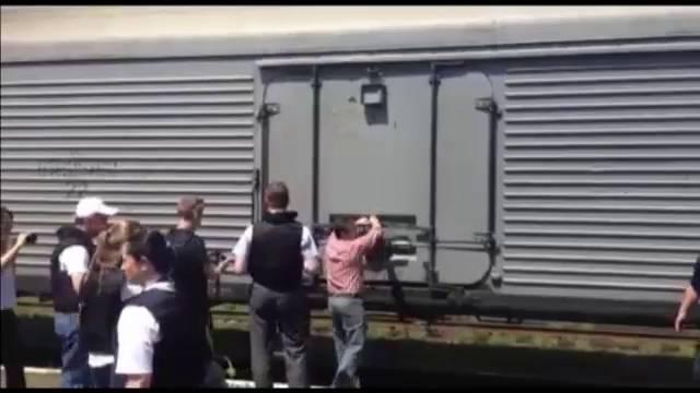 Inspetores da OSCE e legistas holandeses perto do trem onde estão os cadáveres.