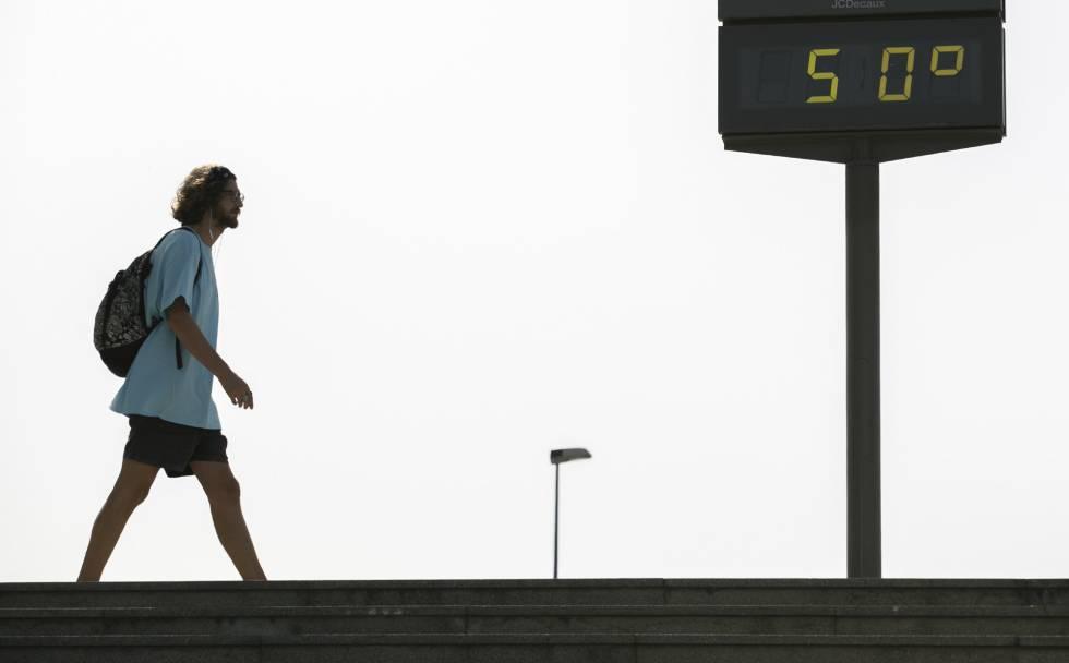 Un hombre camina junto al termómetro situado en el Puente del Cachorro junto a la Torre Sevilla, en una imagen de archivo.