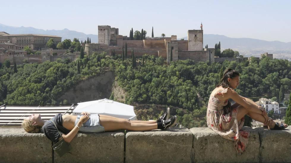 Unos turistas descansan y toman el sol en Granada, en alerta naranja por calor.
