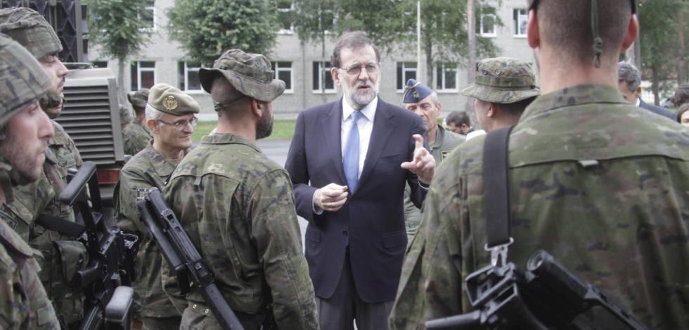 El presidente del Gobierno español, Mariano Rajoy, conversa con varios militares españoles en Letonia.