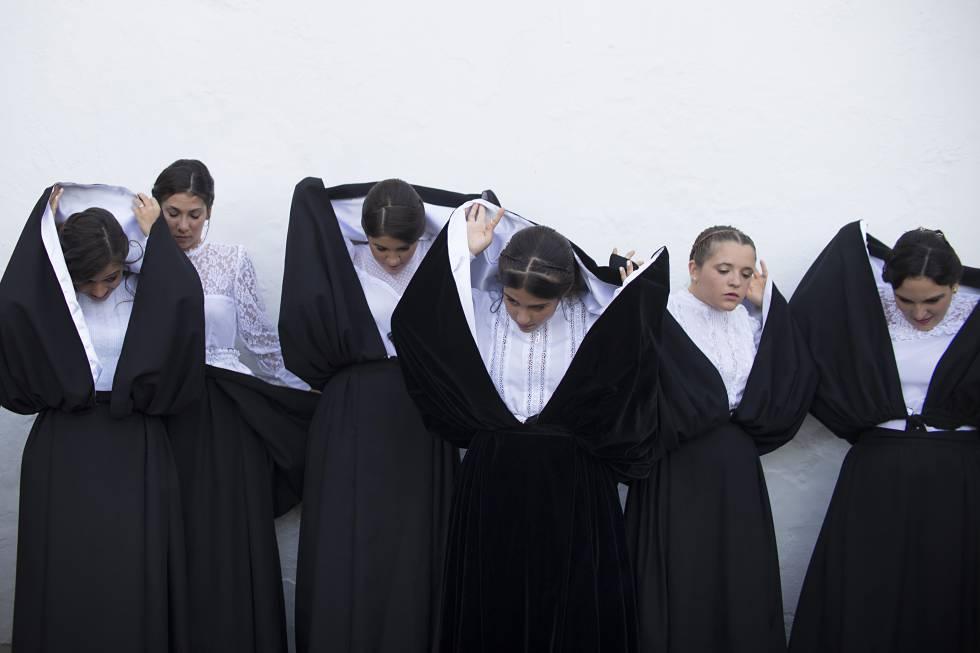 Las mujeres se retiran el manto de la cabeza.