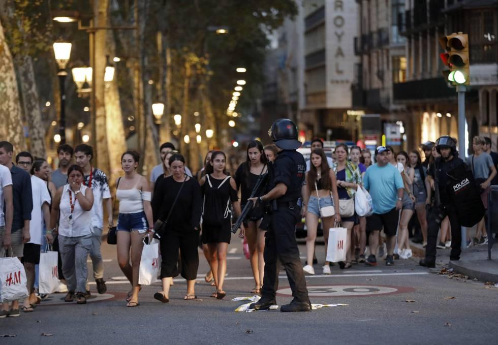Un grupo de gente se desplaza entre el despliegue policial en el lugar del atentado, en las Ramblas de Barcelona.