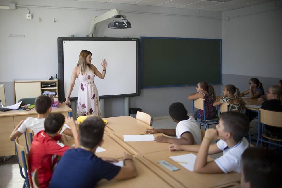 Alumnos de un colegio público en Sevilla siguen la clase con su maestra.