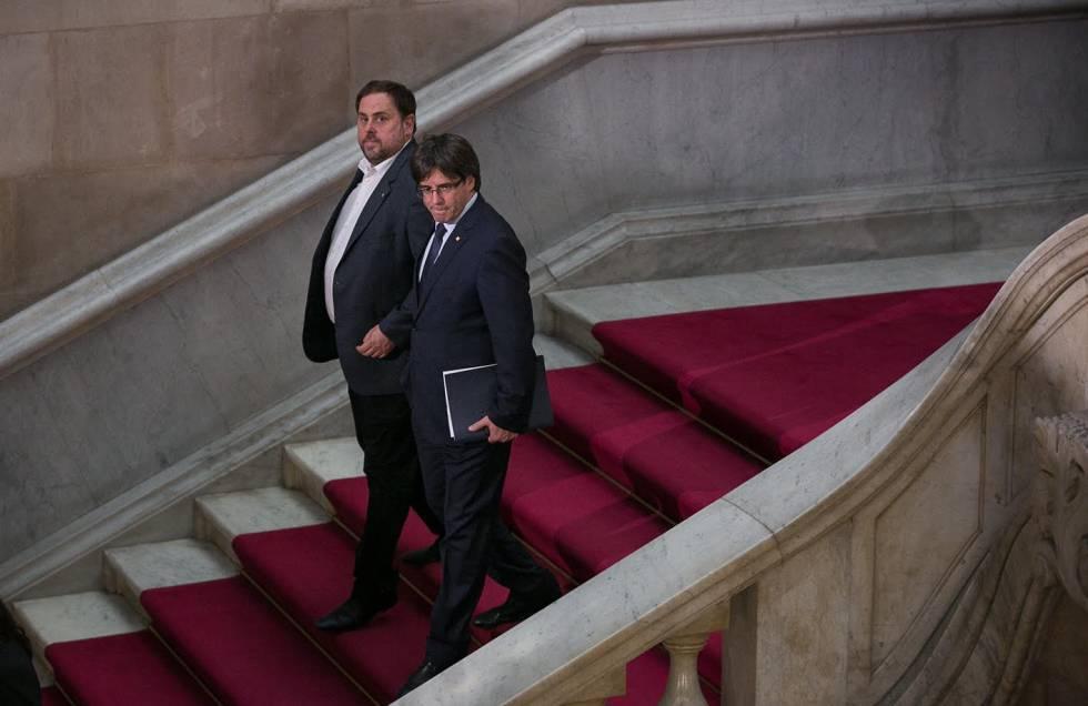 Deputy Catalan Premier Oriol Junqueras (left) and Catalan Premier Carles Puigdemont leave a session of the regional parliament.