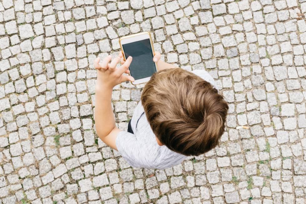 Un niño juega con un móvil.