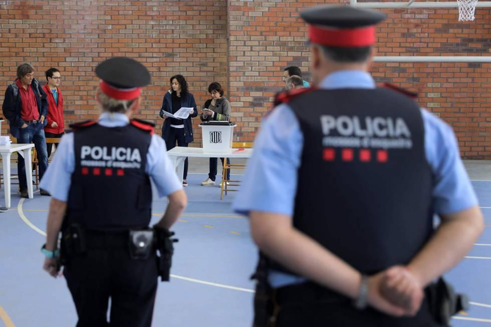 Una pareja de los Mossos, el domingo en un colegio electoral en Figueres.