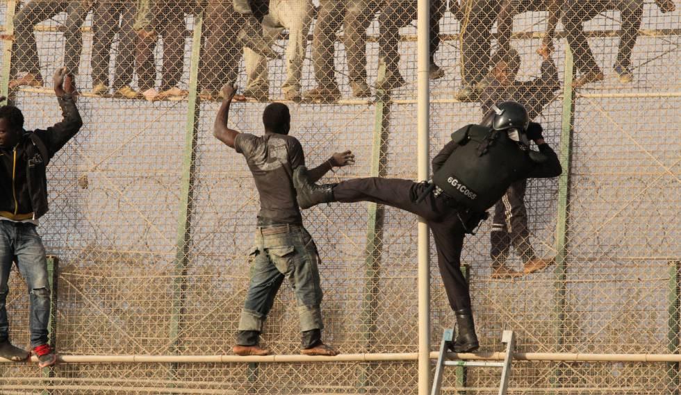 Un grupo de inmigrantes subsaharianos se enfrenta a un policía tras saltar la valla de Melilla.