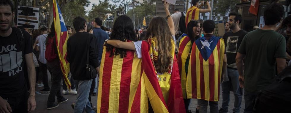 Two girls, one with a Catalan independence flag wrapped on her shoulders walks together with another one with a Spanish flag as demonstrators gather in downtown Barcelona, Spain, Tuesday Oct. 3, 2017. Thousands of people are demonstrated in Barcelona in protest at what they say was police brutality during a referendum on Catalonia's secession from Spain that was previously declared illegal by Spain's Constitutional Court.(AP PhotoSanti Palacios)