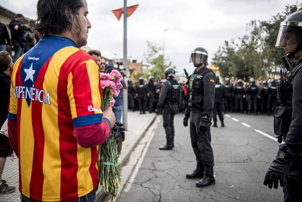 Un manifestante independentista recibe con flores a la Guardia Civil en Sant Julia de Ramis (Girona) el 1 de octubre.